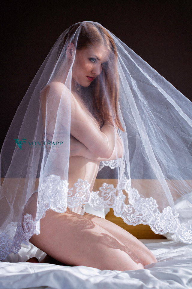Emotive Bridal Boudoir Photo of a nude woman on a bed covered with a bridal veil.