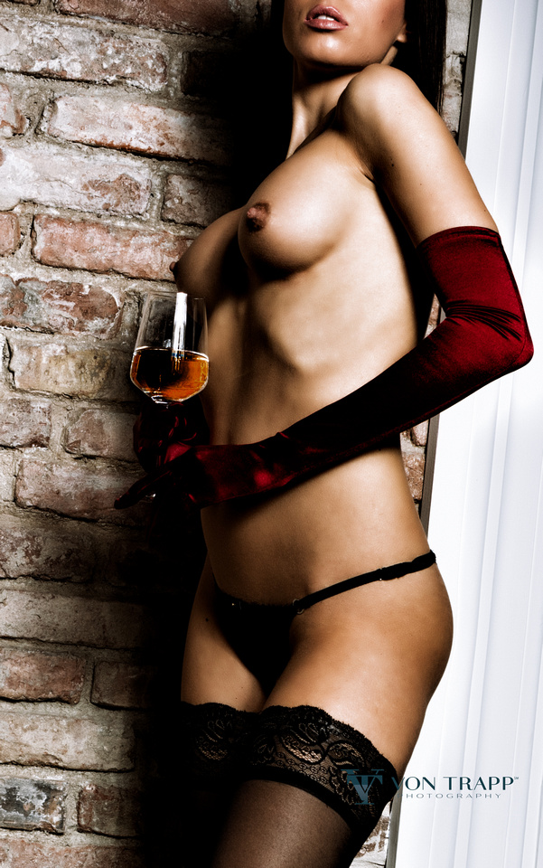 Glamour photo of a topless woman in Budapest wearing elbow length gloves, thong, lace top stockings holding wine glass.