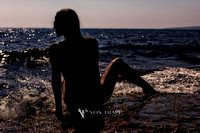 Art nude photo of a woman in shadow sitting on a rock at the surf's edge in Cyprus.