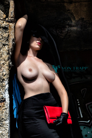 Fashion photo of a busty topless woman wearing a pencil skirt, holding a red purse.