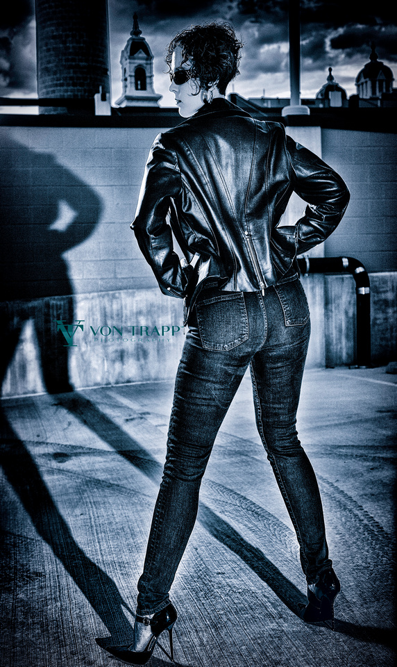 Edgy fashion photo of a woman in stilettos, jeans, and a leather jacket.