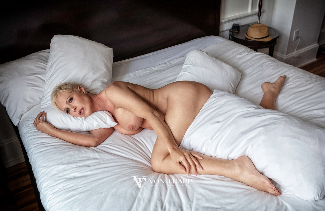 Sexy boudoir photo of a mature woman, nude on a bed.
