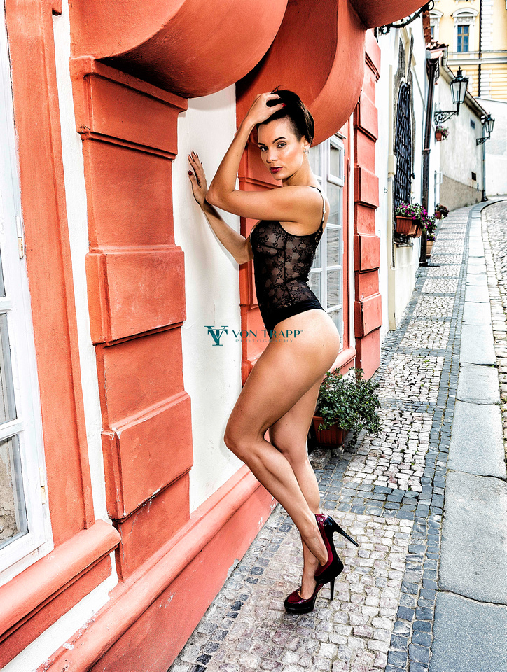 Sexy Czech model wearing a thong bodysuit and heels, out doors on a Prague street.