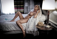 Art-glamour nude photo of a mature woman laying on a bed.