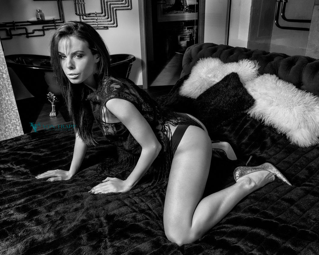 Photo of a smoking hot woman wearing lingerie kneeling on a bed.