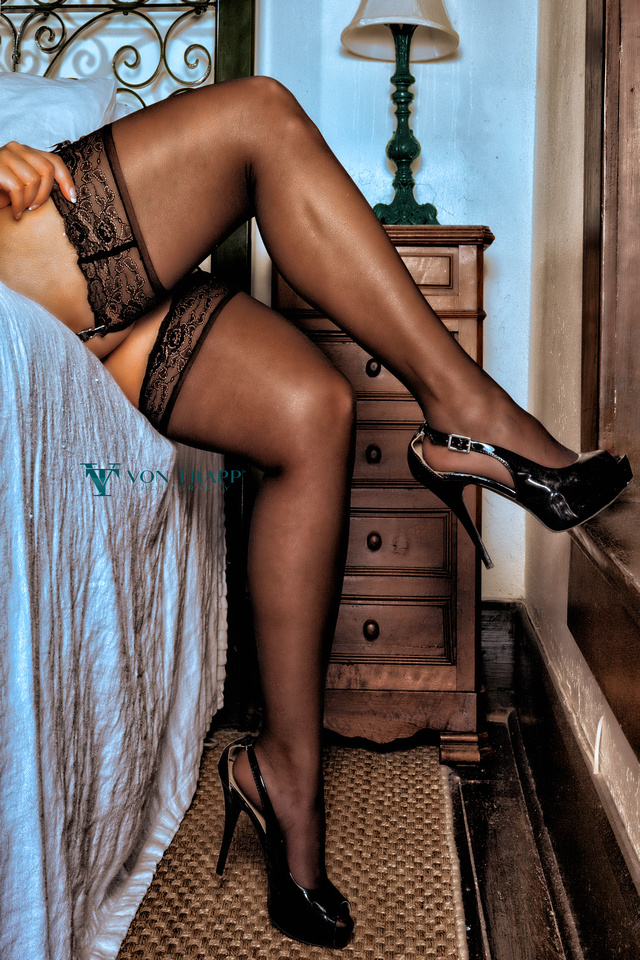 Boudoir photo of a woman's sexy legs in black mlacetop stockings.