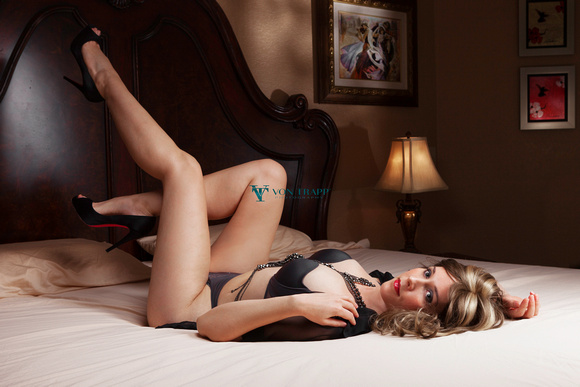 Boudoir photo of a lovely woman laying on a bed with her legs up  wearing lingerie.
