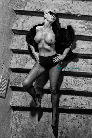 Edgy fashion-glamour photo of a sexy mature beauty, topless in public in San Antonio. Fishnet tights, panty, stilettoes, sunglasses and cape on a staircase.