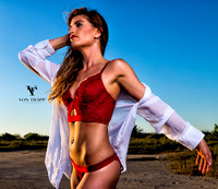 Photo of a sexy long haired woman wearing red lingerie and a sheer white shirt on a Texas beach. Fashion-Glamour photo.
