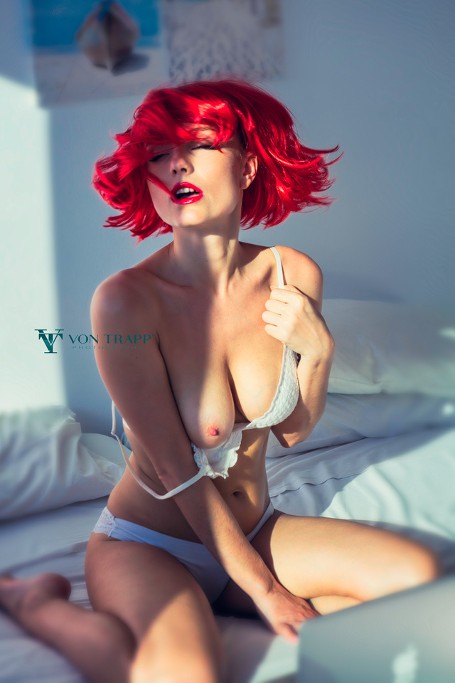 Sexy glamour photo of a topless redhead, taken in a hotel room in Cyprus.