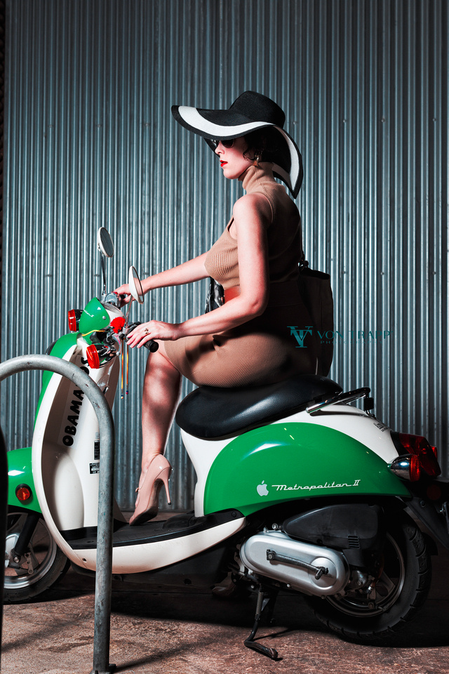 Fashion photo of a voluptuous woman wearing a tight dress and hat on a scooter.