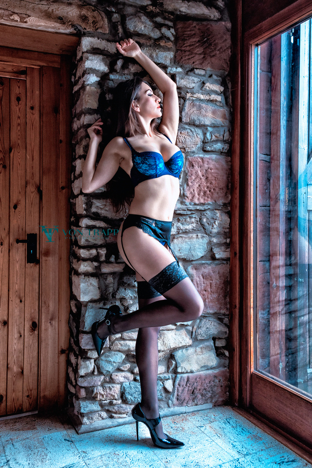 Boudoir Glamour photo of a sexy woman in blue lace lingerie, stockings, garter belt, and stilettoes.