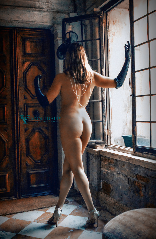 Fashion glamour nude photograph of a leggy blonde in heels, pearls, opera gloves and fascinator, standing at the door to a Venetian palazzo.
