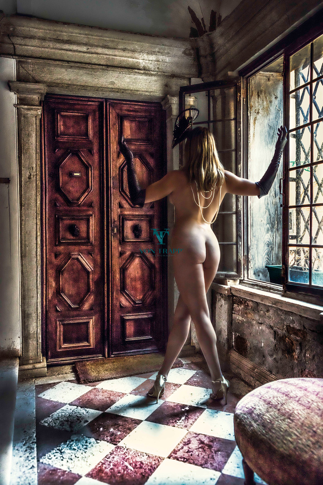 Fashion nude of a nude woman outside the door to an Italian palazzo.