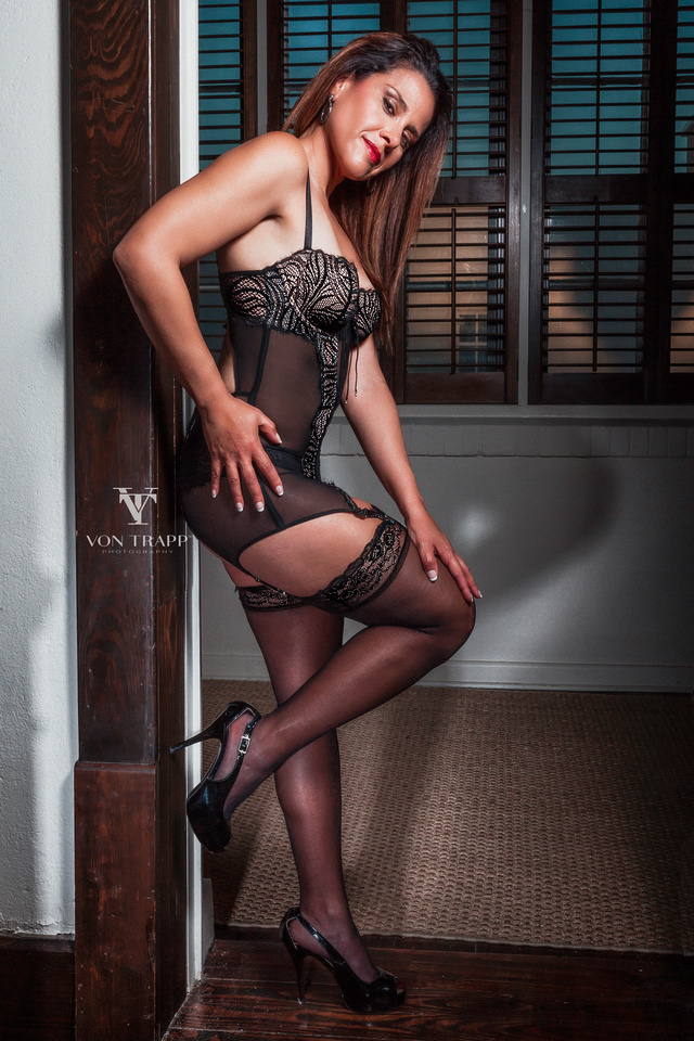Boudoir glamour photograph of a sexy woman in lingerie standing in a doorway.