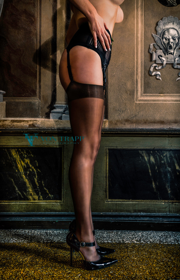 Fashion glamour photo of a topless woman's legs in stockings, garter belt and stilettoes in a Venetian palazzo.