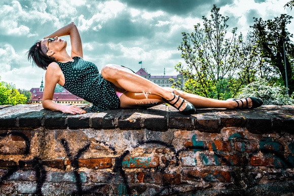 Fashion-Glamour photo of a woman in a short dress giving an upstart in Prague.
