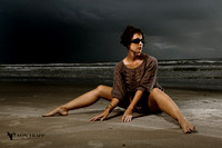 Beautiful glamour photo of a woman taken at a Texas beach with dark storm clouds. Evocative Glamour and Boudoir Photography in Texas.