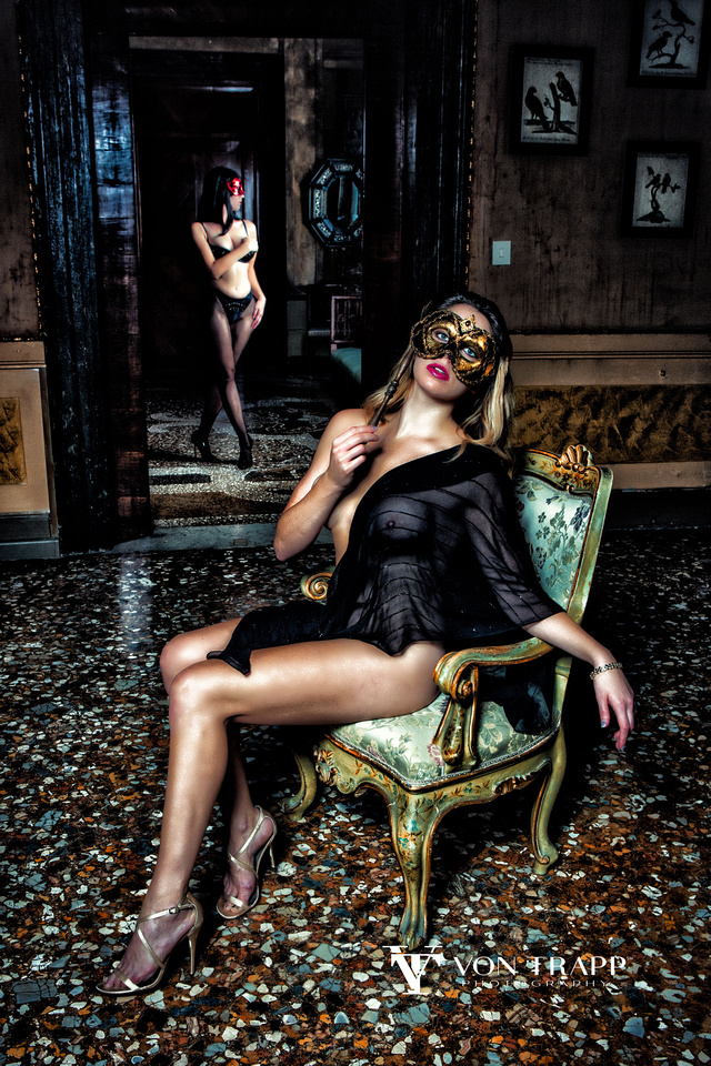 Sexy Fashion photo of two women wearing Venetian masks in a Venice palazzo.