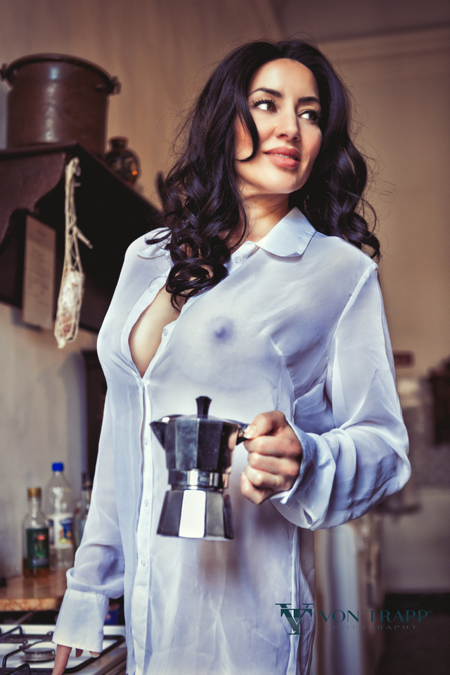 Glamour photo of a woman wearing a sheer white top in a kitchen in a Venice palazzo.