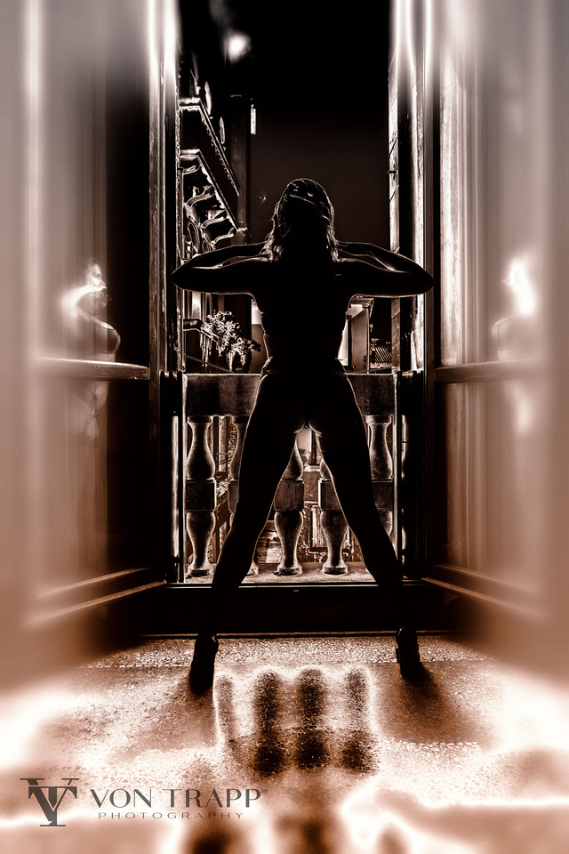 Fashion image of woman at the doorway to a Venice Palazzo balcony wearing lingerie.